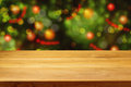 Empty wooden deck table over Christmas tree bokeh background Royalty Free Stock Photo
