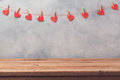 Empty wooden deck table over rustic wall background with heart shape garland. Valentines day