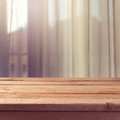 Empty wooden deck table over window curtains background Royalty Free Stock Photo