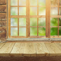 Empty wooden deck table over window and garden bokeh background Royalty Free Stock Photo