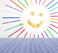 Empty wooden deck table with smiling sun arranged from crayons and pencil sharpening on blue background ready for product displ Stock Photography