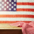 Empty wooden deck table with tablecloth over USA flag bokeh background. 4th of July celebration picnic background. Royalty Free Stock Photo