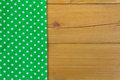 Empty wooden deck table with tablecloth with polka dots green background Royalty Free Stock Photo