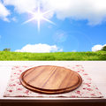 Empty wooden deck table with tablecloth for product montage sunny day blue sky clouds free space for your text Stock Image