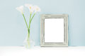 Empty wooden frame and flowers in vase on table on blue background. mock up Royalty Free Stock Photo