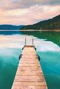 Empty wooden mole on blue alps lake wharf for hired boats in marina ready trip ships Stock Photo