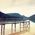Empty wooden mole on blue alps lake wharf for hired boats in marina ready trip ships Royalty Free Stock Photography