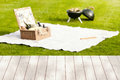 Empty wooden picnic table with hamper and BBQ Royalty Free Stock Photo