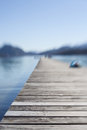 Empty wooden rustic pier or jetty extending out over the calm water of a lake or bay at the seaside with shallow dof Royalty Free Stock Images