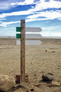 Empty wooden signboard arrow on blurred ocean beach background. Road sign template.