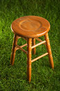 Empty wooden stool on green grass Royalty Free Stock Photo