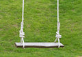 Empty wooden swing in green garden Royalty Free Stock Image