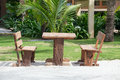 Empty wooden table and chairs of a beach tropical garden near the sea Royalty Free Stock Photo