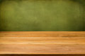 Empty wooden table over grunge green background perfect for product montage Stock Image