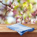Empty wooden table with tablecloth over spring garden bokeh background for product montage Royalty Free Stock Photo