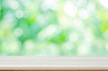Empty wooden table top with blurred green natural abstract background. Royalty Free Stock Photo