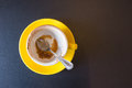 Empty yellow coffee cup over a brown background Royalty Free Stock Photo