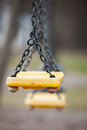 Empty yellow plastic swings on a playground Royalty Free Stock Photography