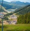 Emtpy chairlift in ski resort. Mountains and hills with in Summer with green trees Royalty Free Stock Photo