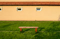 Emty bench on a lawn in a yard and a building in background illuminated by sunset light Royalty Free Stock Image
