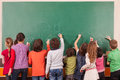 En drgroup of nine pupil drawing on school chalkboard with chalks group children Stock Photo
