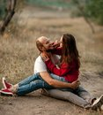 Enamored couple sits, smiles and embraces on forest path. Royalty Free Stock Photo