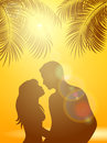Enamored under palm trees on an orange Sunny background Royalty Free Stock Photo