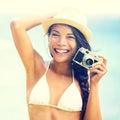 Encalhe mulher com câmera retro do vintage que tem o riso brincalhão do divertimento no biquini no chapéu vestindo da praia do Fotos de Stock Royalty Free
