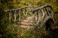 Enchanted bridge this beautiful in the autumn woods appears to be constructed of wood but in fact is made of concrete and steel Royalty Free Stock Photos