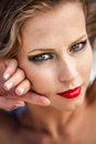 Enchanting eyes close up portrait of a beautiful caucasian model with bright red lips holding her slender fingers to her cheek and Stock Image