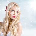 Enchanting snow woman elegant winter style picture of an amazing blonde watching the falling in fashion Royalty Free Stock Photography