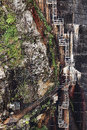 Enclosed industrial ladder view of on rock face next to a hydro electric dam wall Royalty Free Stock Photography
