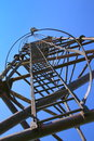Enclosed safety ladder metallic isolated on the blue sky Stock Images