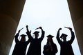End of college outlines four graduates with certificates outside Royalty Free Stock Photography