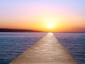 Endless pier wooden at sunset on the sea Stock Photos