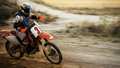 Enduro bike racing along dirt track racer speeding around a curve on motocross Stock Image
