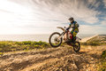 Enduro bike rider climbing a steep slope against a beautiful sunset on a seascape Stock Photos
