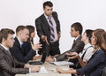 Energetic corporate manager instructs his team six people sit around the table covered by paperwork Royalty Free Stock Photo