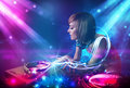 Energetic dj girl mixing music with powerful light effects Royalty Free Stock Images