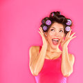 Energetic funny beautiful woman hair style excited pretty in pink wearing rollers curlers and pink dress on pink Royalty Free Stock Photos