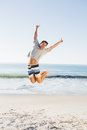 Energetic handsome man jumping on the beach Stock Images