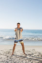 Energetic handsome man showing thumbs up to camera on the beach Royalty Free Stock Images