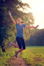 Energetic woman leaping in the air with a happy smile full of vitality as she runs along a country track during a physical workout Stock Photos