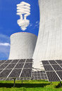 Energy concepts solar panels before a nuclear power plant and bulb from clouds Stock Photo