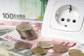 Energy costs socket and many euro banknotes with euro coins Royalty Free Stock Photography