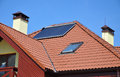 Energy efficiency concept. Closeup of solar water panel heating on red tiled house roof with lightning protection, skylights, Royalty Free Stock Photo