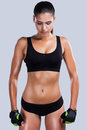 Energy inside her beautiful young sporty woman with perfect body standing against grey background Stock Image