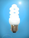 Energy save lamp on a blue background. Royalty Free Stock Photo