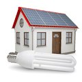Energy saving lamp on the background of the house with solar panels Stock Photography