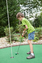 Enfant jouant au golf miniature Photos libres de droits